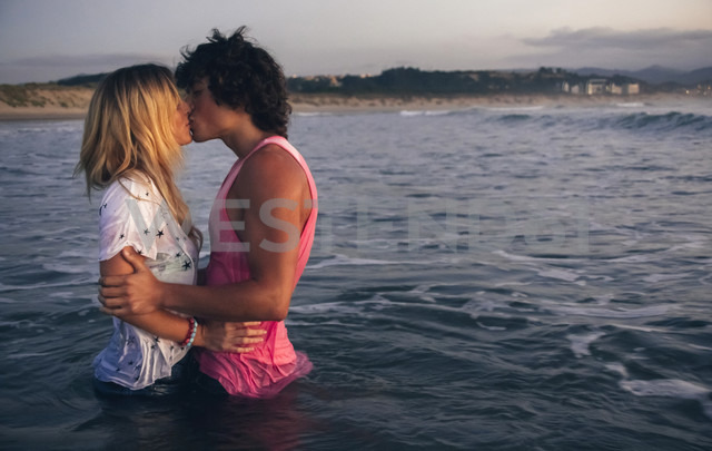 Young couple kissing in the sea at dusk - DAPF00686