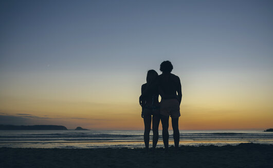 Young couple watching the sunset on the beach - DAPF00689