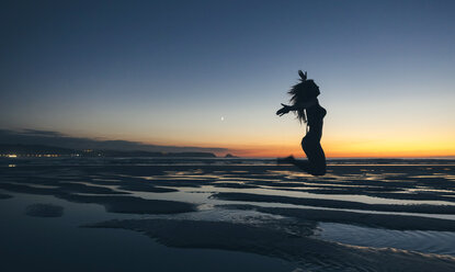 Young woman jumping by the sea at sunset - DAPF00695