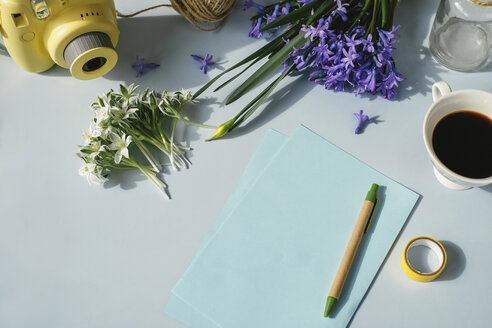 Sheets of paper, camera, cup of coffee and spring flowers on light blue background - MOMF00134