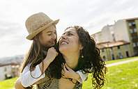 Happy mother carrying daughter outdoors - MGOF03218