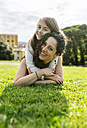 Mother and daughter having fun lying in the grass - MGOF03224