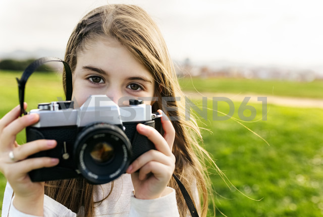 Portrait of a girl holding an old-fashioned camera outdoors - MGOF03230