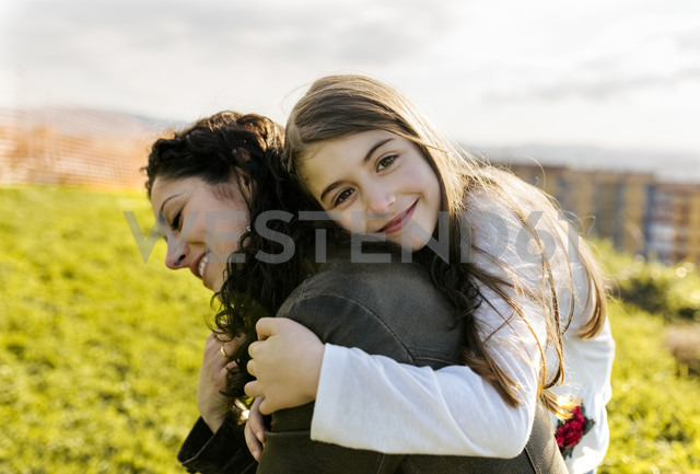 Happy mother carrying daughter outdoors - MGOF03236