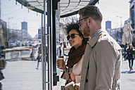 Couple in the city with takeaway coffee looking in shop window - MOMF00142