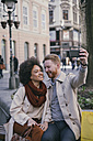 Happy couple taking a selfie in the city - MOMF00148