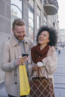 Happy couple in the city with cell phone and shopping bags - MOMF00151