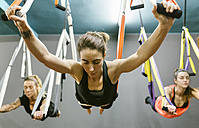 Group of women having a class of aerial yoga - MGOF03254