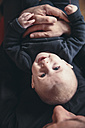 Three-month-old baby being held by father as seen from above - MFF03480