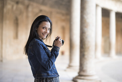 Spain, Granada, smiling young woman with camera at the Alhambra - JAS01671