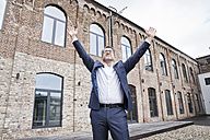 Businessman standing in front of building with arms raised - FMKF03863