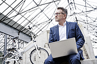 Pensive businessman with laptop - FMKF03890