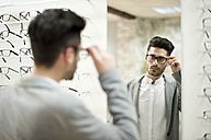 young man trying on glasses at the optician's - JASF01679
