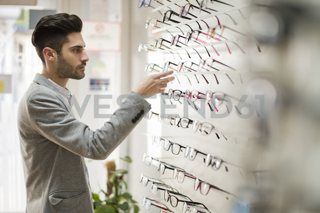 Young man looking for glasses at the optician's - JASF01685 - Jaen Stock/Westend61