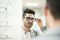 young man trying on glasses at the optician's - JASF01688
