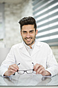 Optician holding glasses in his shop - JASF01691