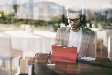Young man sitting in bar, working with digital tablet - JASF01700