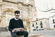Young mna using tablet on a city break - JASF01715