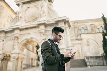 Young mna using tablet on a city break - JASF01718