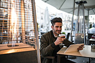 Young man drinking beer in a bar and uses his digital tablet - JASF01721