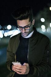 Young man using smartphone at night - JASF01724