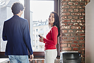 Businesswoman talking to young colleague in office - RHF01866
