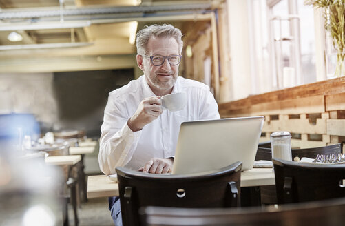 Portrait of confident mature businessman in cafe using laptop - FMKF03914