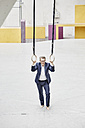 Confident mature businessman standing at gymnastic rings - FMKF03923