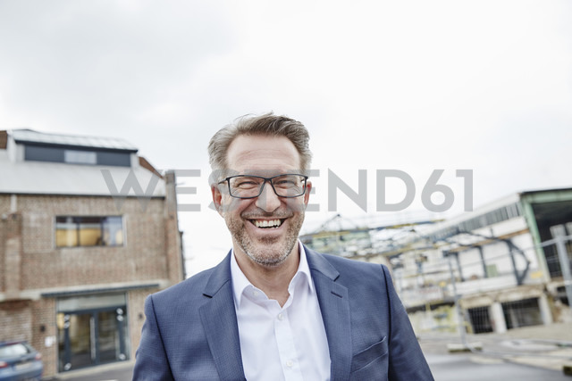 Portrait of laughing mature businessman outdoors - FMKF03926