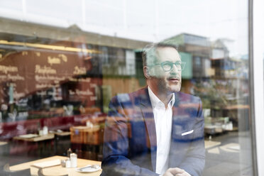 Confident mature businessman looking out of window - FMKF03935