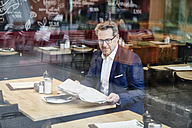 Mature businessman in cafe reading newspaper - FMKF03938