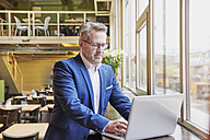 Mature businessman in cafe using laptop - FMKF03944