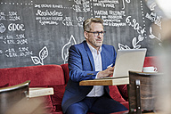 Mature businessman in cafe using laptop - FMKF03950