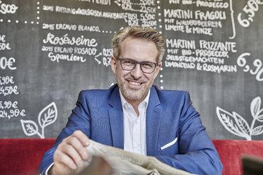 Portrait of smiling mature businessman in cafe reading newspaper - FMKF03953