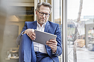 Mature businessman using tablet at the window - FMKF03962