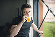 Young man drinking an orange juice at the window - RAEF01831