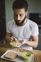 Young man having breakfast at home, toast with avocado cream - RAEF01837