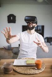 Man having breakfast wearing virtual reality glasses - RAEF01840