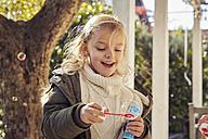 Happy girl in garden making soap bubbles - KDF00718