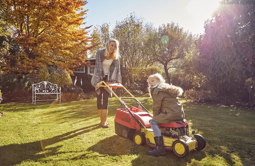 Mother with daughter in garden lawnmowing - KDF00721