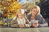 Mother with daughter at garden table using cell phones - KDF00727