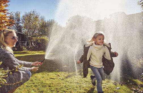 Mother and daughter playing with garden hose in autumn - KDF00730