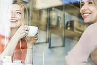Two smiling young women in a cafe looking out of window - FMOF00213