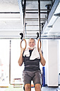 Fit senior man in gym working out on rings - HAPF01465