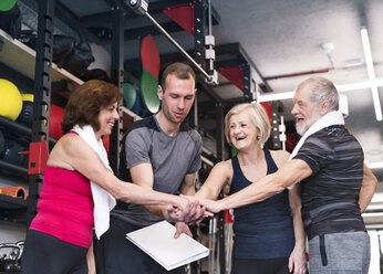 Group of fit seniors with personal trainer in gym - HAPF01468
