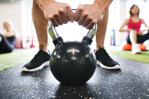 Close-up of man exercising with kettlebell in gym - HAPF01474
