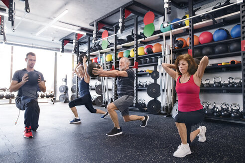 Group of fit seniors with personal trainer in gym exercising with medicine balls - HAPF01477