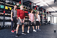 Group of fit seniors with personal trainer in gym - HAPF01483