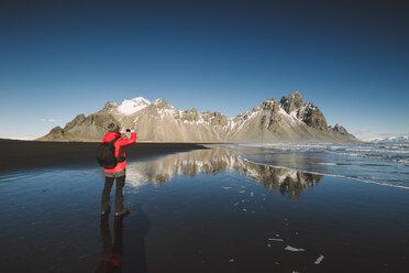 Iceland, man taking a photo at Vestrahorn mountain - RAEF01843