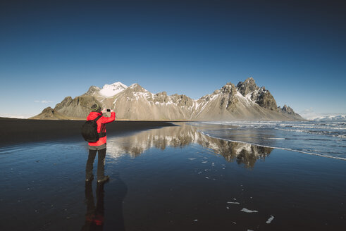 Iceland, man taking a photo at Vestrahorn mountain - RAEF01843